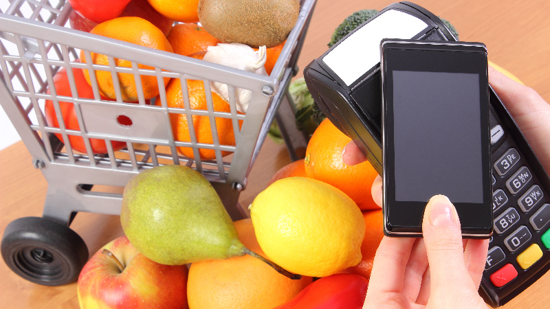 Picture of person buying fruits using phone and NFC wireless pay terminal.
